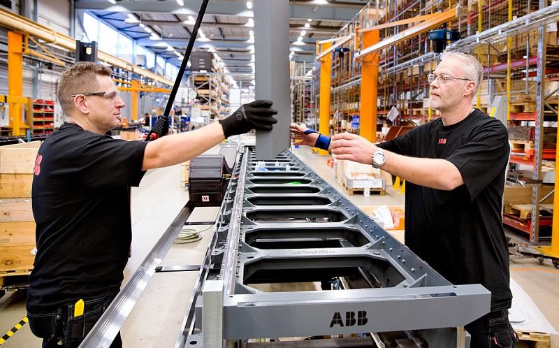 """Hantverk. I robotfabriken är det inte robotarna som gör jobbet. Det nödvändiga finliret finns i montörernas händer. """"Man måste småfibbla lite"""", säger Peter Hill och Johnny Olsson som monterar en åkbana för robotar. """"Vi bygger bort andras jobb, tyvärr. Det känns lite dubbelt""""."""