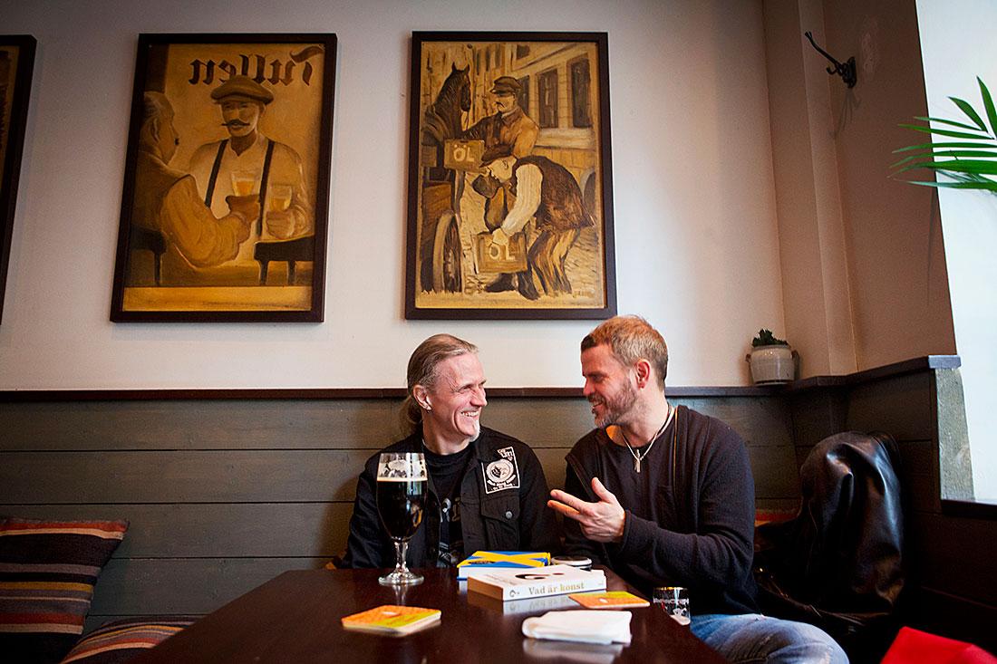 """Två läsande verkstadsarbetare. Stefan Löfgren lyssnar när Anders Olofsson berättar om när han ville köpa en bok av Alice Munro: """"Expediten ville inte rekommendera någon till mig eftersom Munro uppskattas mest av kvinnor. Jag gav mig inte, men utan resultat. I stället tipsade hon om Johan Theorin för spänningens skull, ett helt okej tips. Men ändå häpnadsväckande att jag inte fick köpa Alice Munro."""" Foto: Niklas Maupoix"""