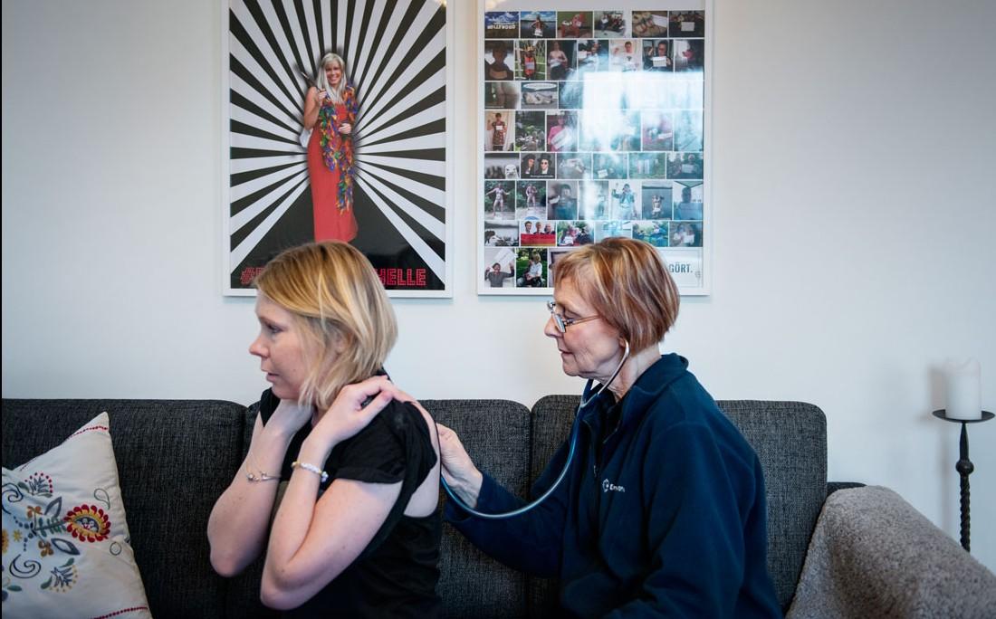 Helena Peltola fick avancerad sjukvård i hemmet via Ersta sjukhus. Läkaren Charlotta Gauffin undersöker henne och på väggen bakom hänger vännernas kampanj, inramade bilder från galna ögonblick i livet.