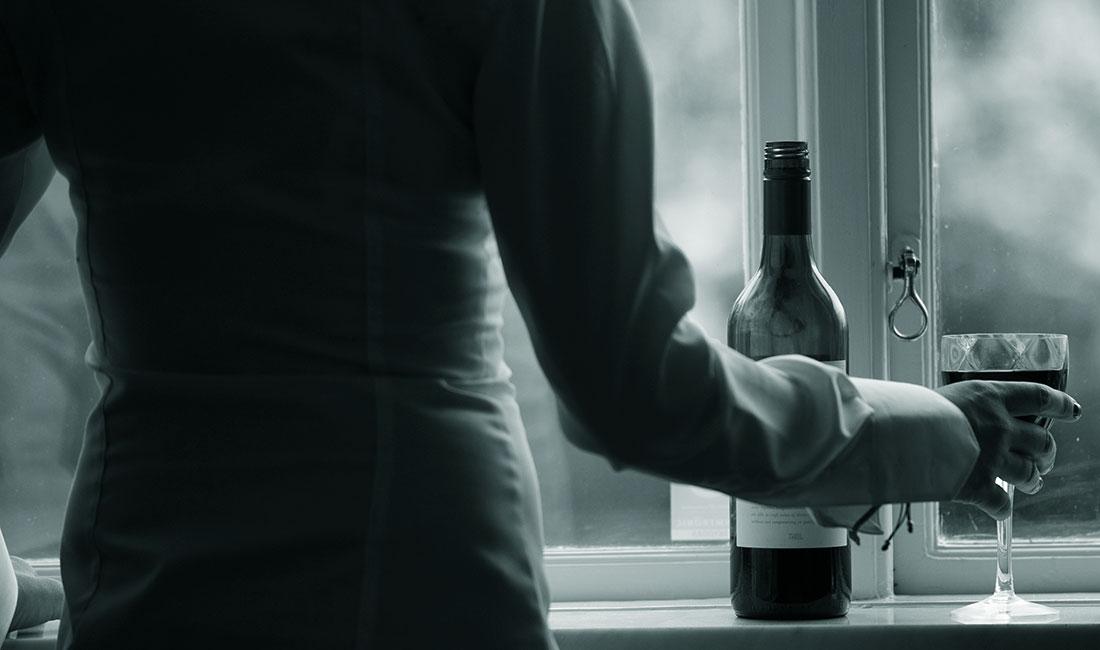 Person som drickr vin vid ett fönster