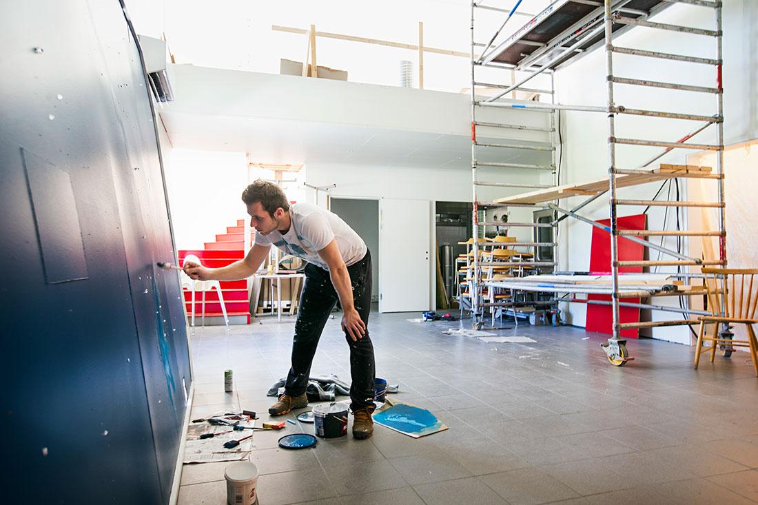 Fotbollslaget räddade byns affär och spelarna hjälper till med renoveringen. Yasmin Campara lämnade Bosnien för att spela i Nordvärmlands FF. På fritiden hjälper han till att måla det som ska bli butikens restaurang och kafé i Ambjörby. Foto: ØYVIND LUND
