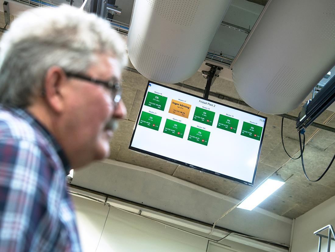 Bättre överblick har ökat effektiviteten. Ekonomichefen Sören Larsson kollar monitorn i taket som visar hur formsprutnings- maskinerna går. Sju kör för fullt medan en håller på att ställas om. Foto: Anna Sigge