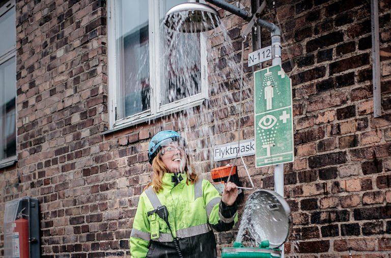 """Emma Davidsson testar nödduschen vid """"Ättikan"""" – där en gång Perstorpsättikan tillverkades. Halva dagen sitter processoperatörerna i kontrollrummet, andra halvan är de ute i tillverkningen. Foto: David Lundmark"""