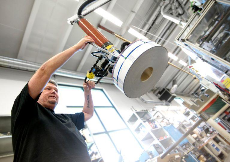 Rullarna med etiketter som ska lyftas ur maskinen och packas i kartonger väger 14 kilo. Det låter inte så tungt – men 60 rullar på en dag blir 840 kilo. Foto: Anna Sigge