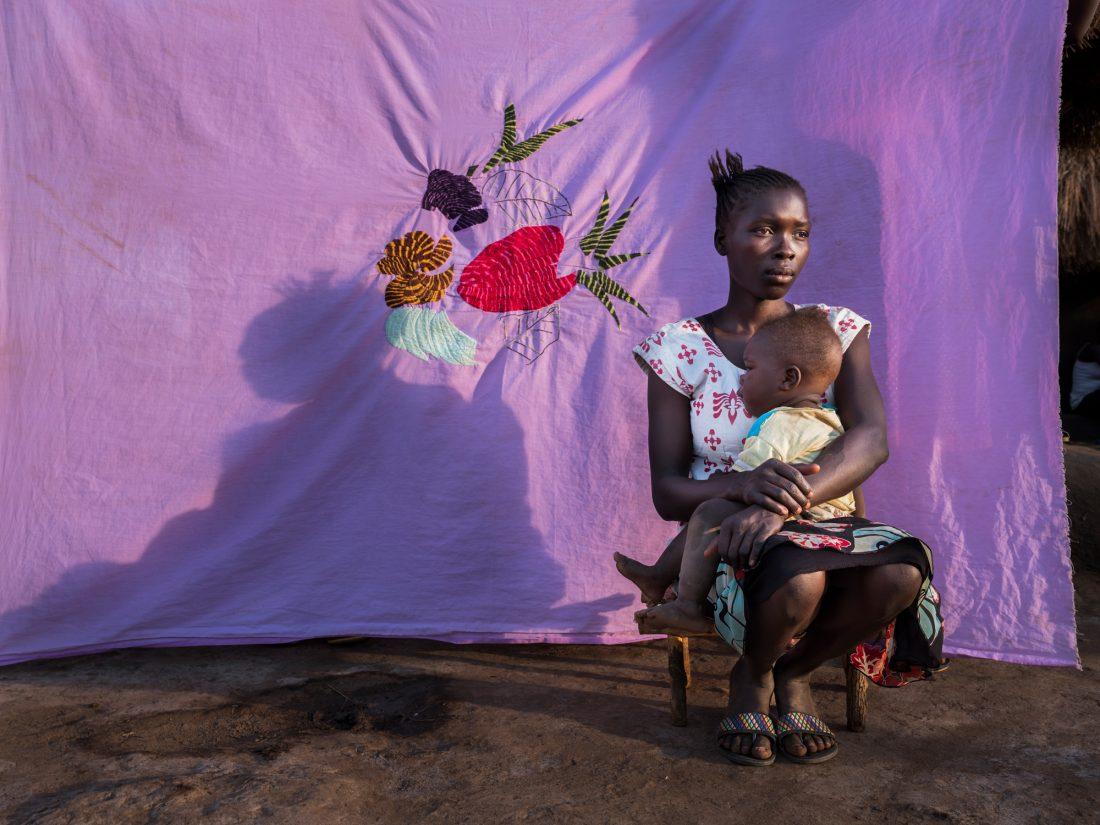 """Esther Pond och Emmason Gift. """"I Sydsudan kom folk på natten, knackade på dörrar och frågade om din man var hemma. Om han var där, dödade de honom och många kvinnor blev våldtagna. Så efter att ha hört alla dessa historier var jag tvungen att lämna. Vi började vår resa på morgonen, jag hade packat mitt Milaya och kläder. På vägen hit tänkte jag bara på att jag aldrig skulle varit här idag om inte kriget tvingade mig"""", berättar Esther Pond, 19 år gammal med sin dotter Emmason Gift, 7 månader gammal och född i Bidibidi. Foto: Nora Lorek"""