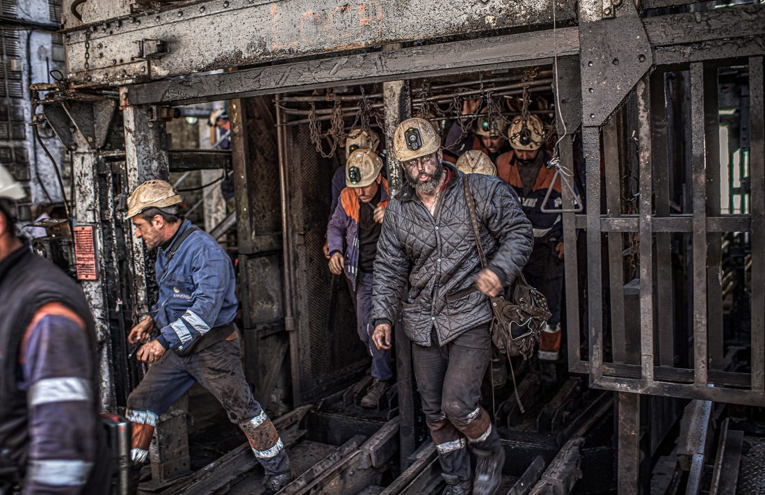 Gruvarbetare kommer upp ur gruvan