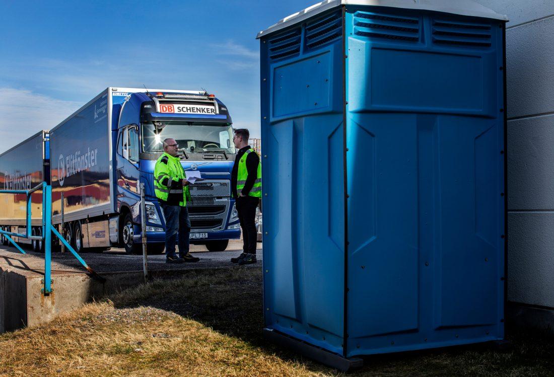 Lastbilsförare lämnar och hämtar leveranser hela dagarna. För att undvika smittspridning mellan dem och de anställda på Elitfönster, har företaget ställt ut bajamajor runt om fabriken. Foto: Åke Ericson