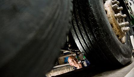 Christer Gustavsson utsätts för mycket droppande vatten när snön smälter. Under vintern har debatten om vinterdäck på lastbilar aktualiserats. Enligt flera mekaniker på Volvo Truck Center behövs inga vinterdäck om mönsterdjupet är tillräckligt på sommardäcken. Foto: ANDERS G WARNE