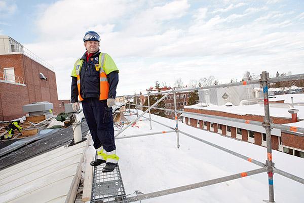 Fyra våningar upp pågår reparationer av taket. Snö och is ökar halkrisken. Räcket består av väl förankrade rör och håller även om huvudskyddsombudet Lasse Johansson ramlar mot det.   Foto: TOMAS BERGMAN