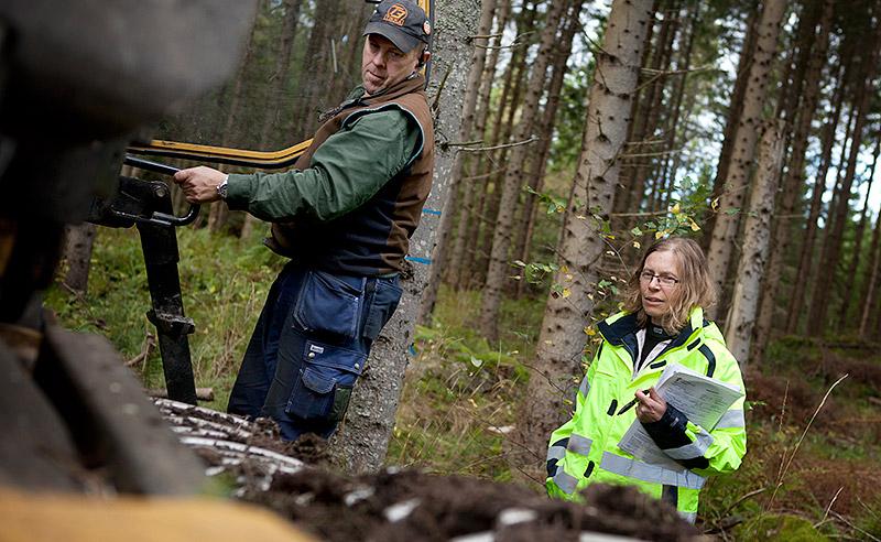 Tommy Wiström visar Pernilla Bergman att skördarens aggregat stannar när hyttens dörr öppnas. Foto: STINA JÄRPERUD