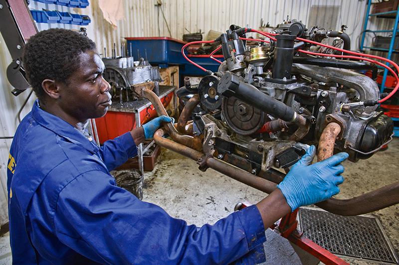 Olubunmi Sodunke fixar de sista detaljerna på en motor innan han återvänder till Nigeria. Han hoppas på arbetstillstånd   och jobb i Sverige nästa år igen. Foto: ERLAND SEGERSTEDT