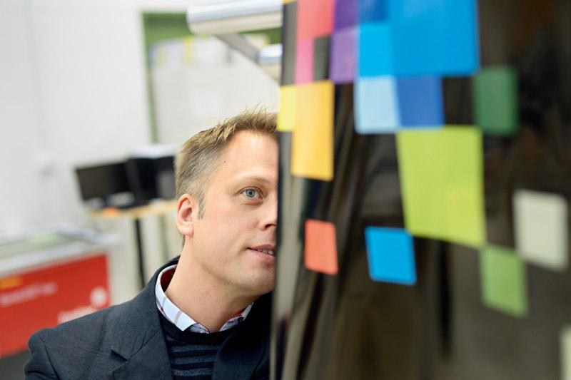 Tommy Höglund visar de tryckta lednings-banorna på baksidan av den blinkande roll-upen. Den lysande tryckfärgen har utvecklats under flera år och nu har ett företag – Lumisigns – bildats och fått sina första beställningar att leverera.  Foto: BRITA NORDHOLM