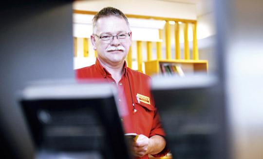 Olle Johansson, nybliven läsambassadör som tar hand om böcker och bokhyllor på Sandvik Coromant Foto: GUN WIGH