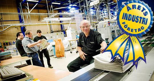 Kjell Schröder jobbar i packsalen på BTT. Med många års erfarenhet i branschen kan han jämföra med andra arbetsplatser. Här har de som jobbar i produktionen inflytande över arbetsmiljön, tycker han. I bakgrunden kikar skyddsombuden André Toivonen, Håkan Haglund och Torleif Roos i ett alldeles färskt exemplar av lokaltidningen Väster.  Foto: JONAS LINDSTEDT