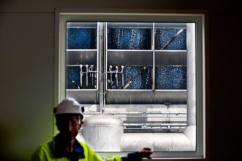 Jörgen Agebjörn i den stora kondensturbinhallen, från vilken den använda ångan leds till kyltornet, som syns genom fönstret, för återvinning. Foto: JAN NORDSTRÖM